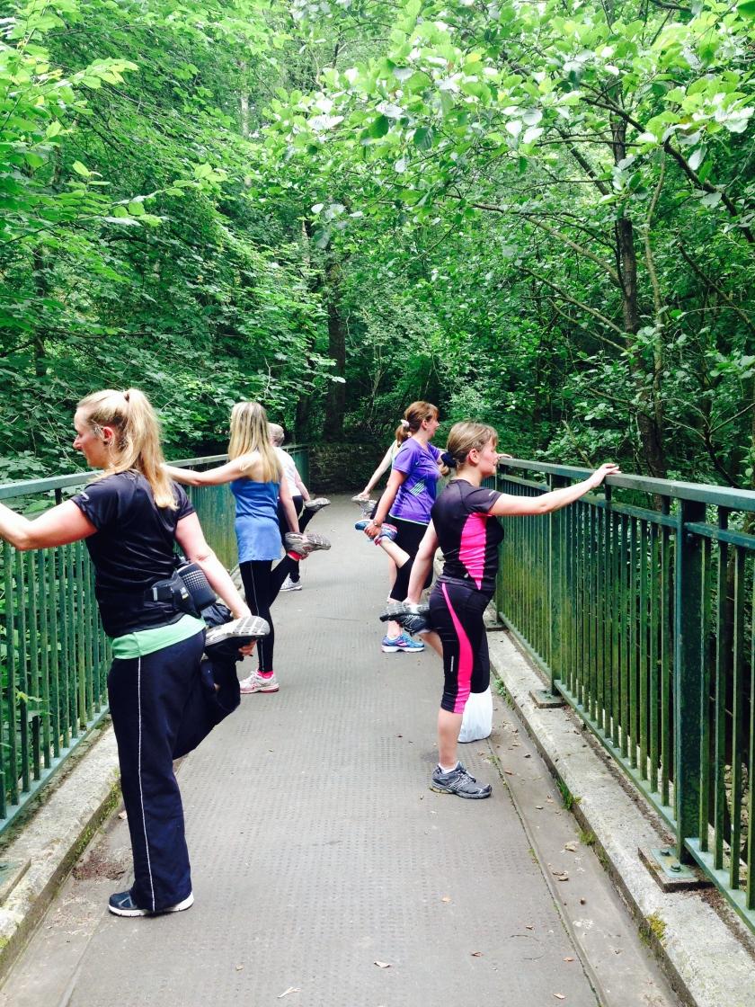 Women stretching on bridge in woodland