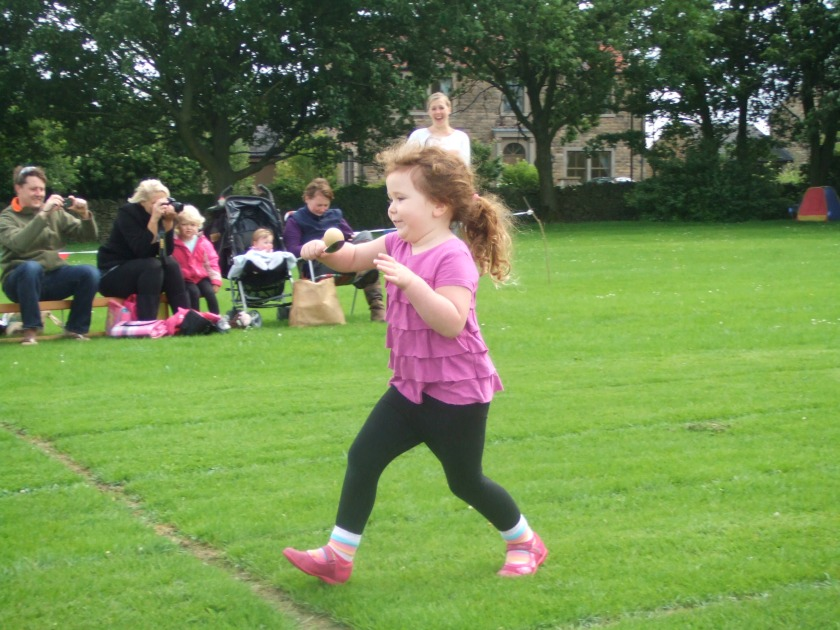 Child running egg and spoon race